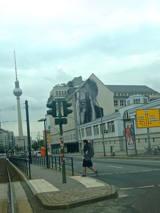 A street art work by French artist, JR, peeks out against a background of the Fernsehturm, the Berlin TV tower