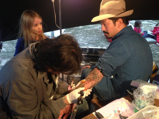 Japanese tattoo artist at work in the Bearded Lady tent